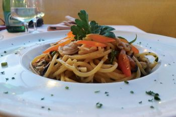 Homemade spaghetti with seafood, yellow cherry tomatoes and green chilies