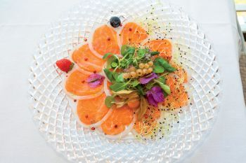 Salmon and squid carpaccio with corn salad flavored with lime and pink pepper